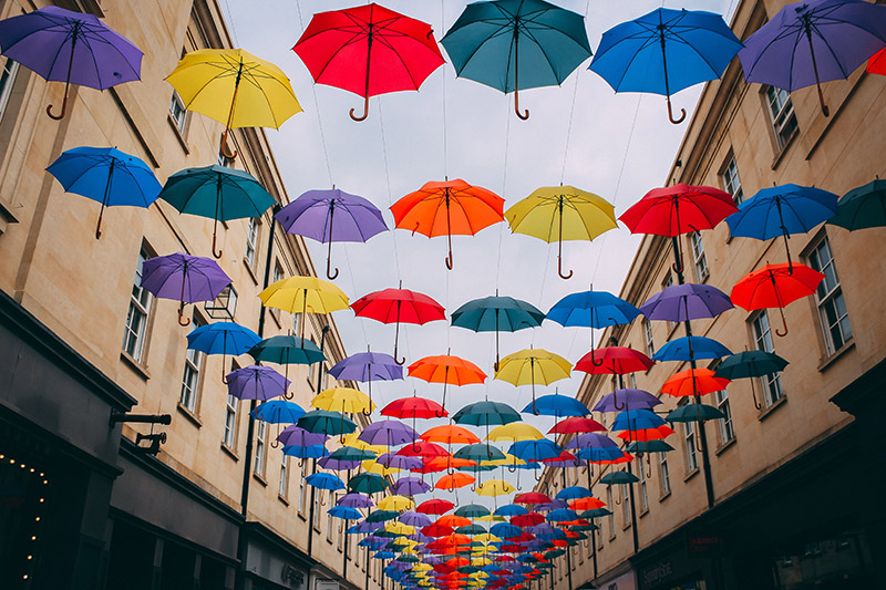 Photo of many colourful umbrellas suspended in rows across a street