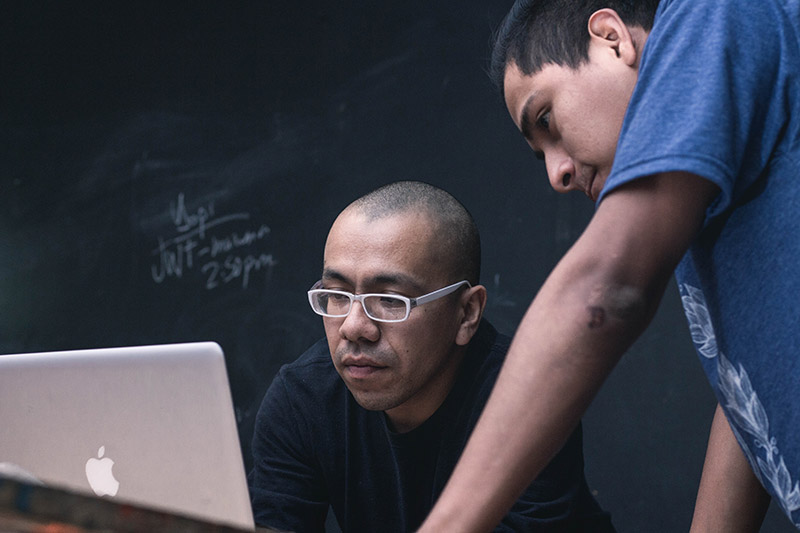 Photo of two men looking at a laptop
